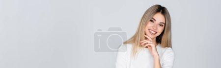 Photo pour Joyeux jeune femme en tenue blanche souriant isolé sur gris, bannière - image libre de droit