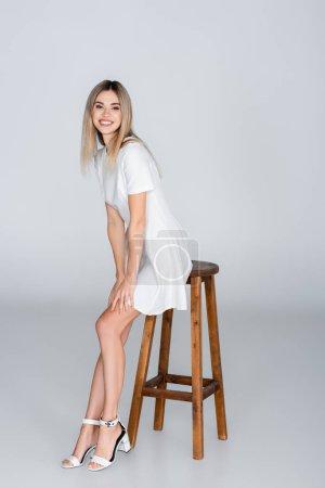 Photo pour Pleine longueur de gaie jeune femme en robe blanche souriant tout en étant assis sur tabouret sur gris - image libre de droit