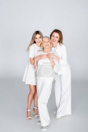 Photo pour Pleine longueur de trois générations de femmes heureuses souriant tout en regardant la caméra sur gris - image libre de droit
