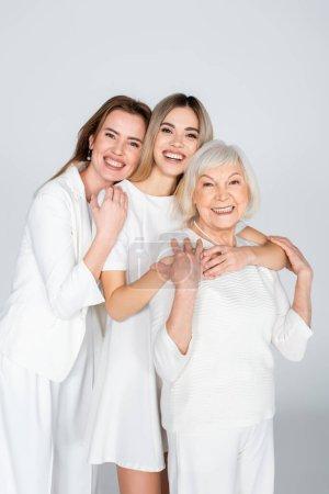 Photo pour Trois générations de femmes souriantes regardant caméra et câlins isolés sur gris - image libre de droit