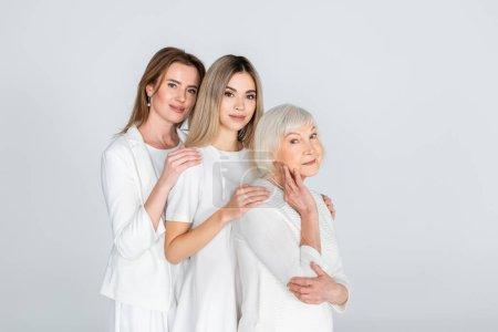 Photo pour Trois générations de femmes joyeuses souriant en regardant la caméra et étreignant isolé sur gris - image libre de droit