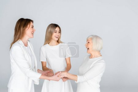 three generation of joyful women smiling while holding hands isolated on grey