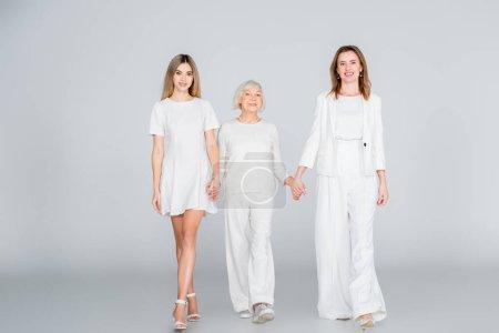 Photo pour Pleine longueur de trois générations de femmes heureuses souriantes tout en se tenant la main et en marchant sur le gris - image libre de droit