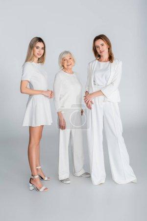 Photo pour Pleine longueur de trois générations de femmes heureuses souriant tout en se tenant sur le gris - image libre de droit