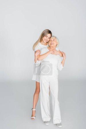Photo pour Pleine longueur de joyeuse petite-fille embrassant grand-mère heureuse sur gris - image libre de droit