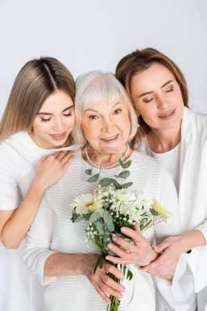 Photo for Happy senior woman smiling while holding flowers near daughter and granddaughter isolated on white - Royalty Free Image