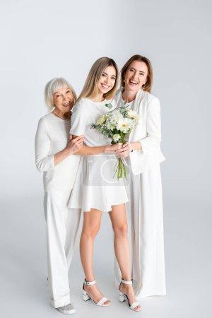 Photo pour Pleine longueur de jeune femme heureuse souriant tout en tenant des fleurs près de la mère et mamie sur gris - image libre de droit