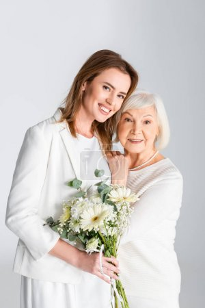 Photo for Cheerful daughter holding flowers and smiling with happy senior mother isolated on grey - Royalty Free Image
