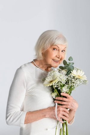 Photo for Happy retired woman with grey hair holding flowers isolated on grey - Royalty Free Image