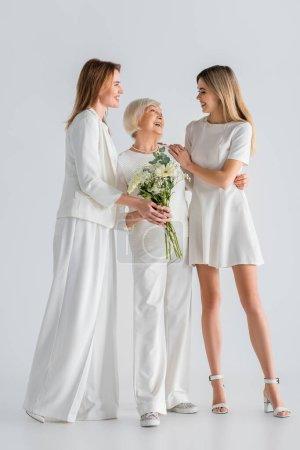 Photo pour Pleine longueur de femme âgée heureuse tenant des fleurs et souriant avec sa fille et sa petite-fille sur gris - image libre de droit