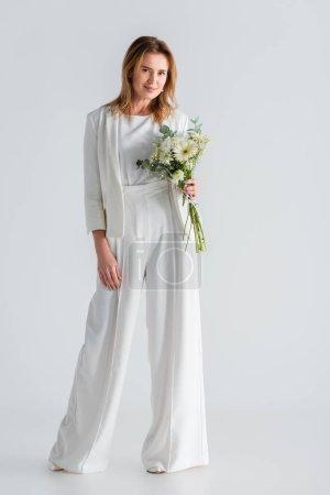 Photo pour Pleine longueur de femme en tenue blanche tenant des fleurs sur gris - image libre de droit