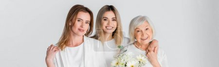 three generation of happy women smiling while hugging near flowers isolated on grey, banner