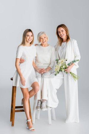 Photo pour Pleine longueur de femme heureuse tenant des fleurs et souriant tout en étant assis sur la chaise avec fille et mère sur gris - image libre de droit
