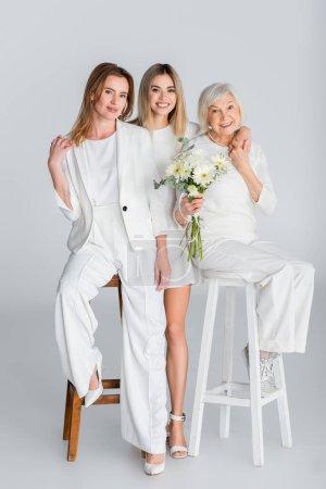 Photo pour Pleine longueur de femme âgée heureuse tenant des fleurs et souriant tout en étant assis sur la chaise avec sa fille et sa petite-fille sur gris - image libre de droit