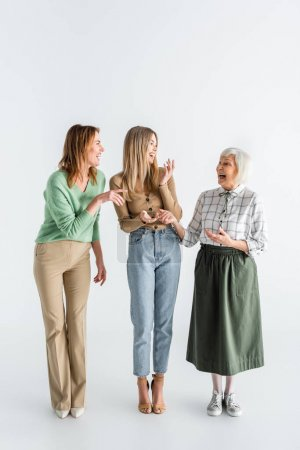 Photo for Full length of three generation of happy women laughing while standing on white - Royalty Free Image