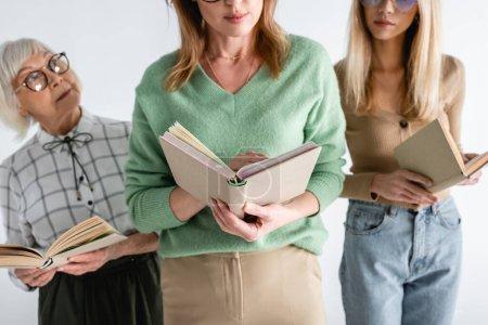 drei Generationen intelligenter Frauen in Brillen, die Bücher isoliert auf weißem Papier lesen