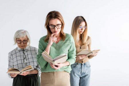 Photo for Three generation of intelligent women in glasses reading books isolated on white - Royalty Free Image