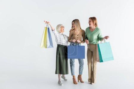 Photo for Full length of three generation of joyful women holding shopping bags on white - Royalty Free Image