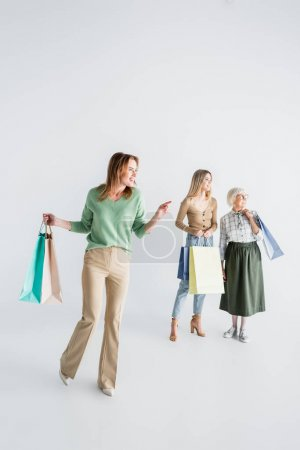 Photo for Full length of happy woman holding shopping bags and pointing with finger near daughter and senior mother on blurred white background - Royalty Free Image