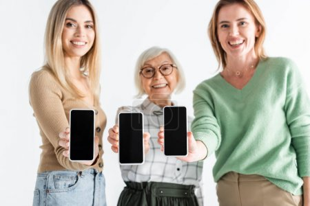 three generation of happy women holding smartphones with blank screen isolated on white