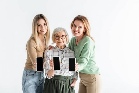 Photo for Three generation of cheerful women holding smartphones with blank screen isolated on white - Royalty Free Image