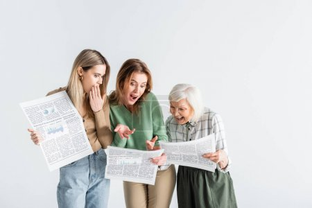 three generation of surprised women reading newspapers isolated on white