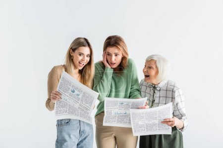 Photo for Three generation of astonished women reading newspapers isolated on white - Royalty Free Image