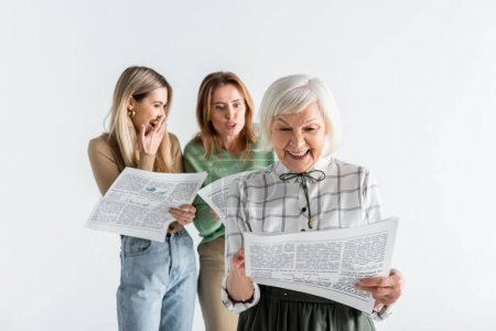 Photo for Cheerful senior woman reading newspaper near daughter and granddaughter on blurred background isolated on white - Royalty Free Image