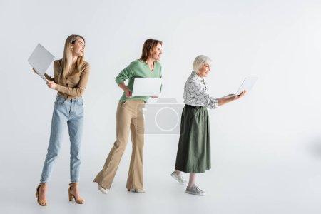 Foto de Longitud completa de tres generaciones de mujeres alegres sosteniendo computadoras portátiles en blanco - Imagen libre de derechos