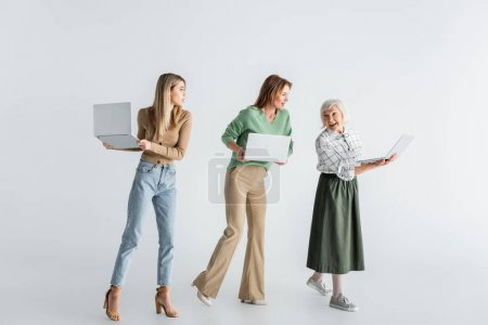 full length of three generation of women with laptops on white