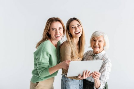 three generation of happy women looking at camera near laptop isolated on white