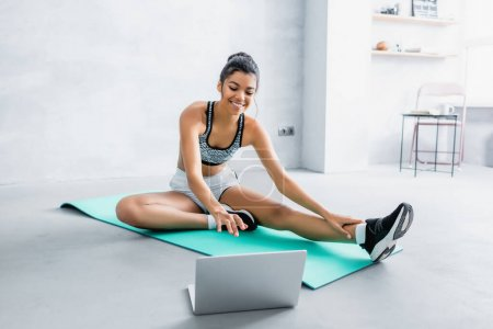 smiling african american woman in sportswear sitting on fitness mat near laptop at home