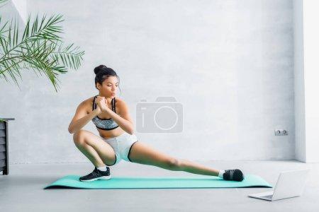 Photo pour Jeune sportive afro-américaine faisant des exercices d'étirement sur un homme de fitness près d'un ordinateur portable - image libre de droit