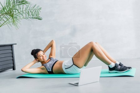 cheerful african american woman doing abs exercise near laptop at home