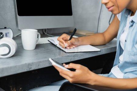 Photo pour Vue recadrée d'un pigiste afro-américain utilisant un téléphone portable et écrivant dans un carnet près d'une tasse de thé et d'un ordinateur, au premier plan flou - image libre de droit