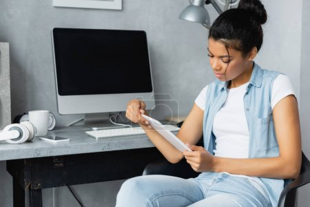 young african american freelancer holding digital tablet while sitting near monitor with blank screen