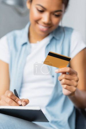 smiling african american woman holding credit card and writing in notebook, blurred foreground