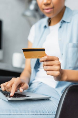 partial view of african american woman holding credit card while using laptop, blurred foreground