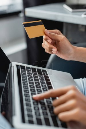 partial view of african american woman typing on laptop while holding credit card, blurred foreground