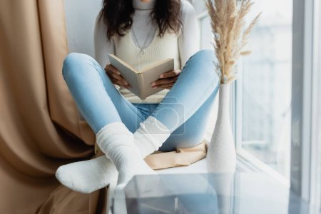 cropped view of african american woman reading book while sitting on windowsill with crossed legs