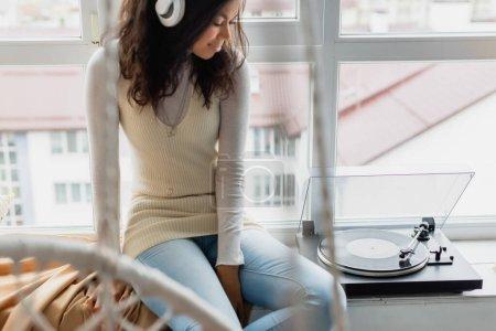 Photo pour Jeune femme afro-américaine dans des écouteurs sans fil assis près du tourne-disque sur le rebord de la fenêtre, au premier plan flou - image libre de droit