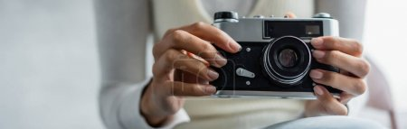 cropped view of african american woman holding vintage camera, blurred foreground, banner