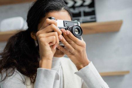 Photo pour Jeune femme afro-américaine prenant des photos sur appareil photo vintage à la maison - image libre de droit