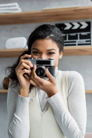 Photo pour Positive femme afro-américaine prenant des photos sur caméra vintage à la maison - image libre de droit
