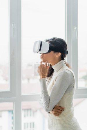 femme afro-américaine réfléchie dans un casque vr regardant par la fenêtre à la maison
