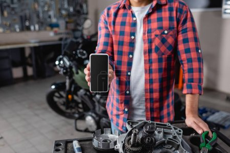 Photo for Cropped view of mechanic holding smartphone with blank screen near motorbike spare parts, blurred background - Royalty Free Image