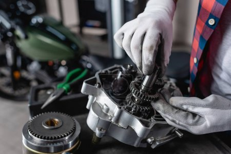 partial view of technician in gloves examining disassembled motorbike gearbox