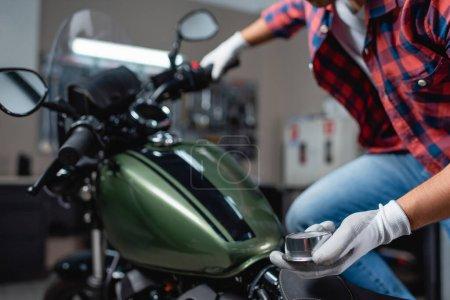 Photo pour Vue recadrée du technicien tenant manomètre tout en mesurant la pression d'air dans le pneu de la moto, avant-plan flou - image libre de droit