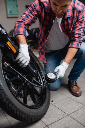 Photo pour Réparateur mesurant la pression dans le pneu de la moto avec manomètre - image libre de droit