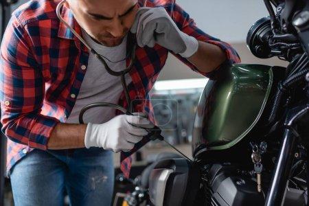 Photo pour Jeune mécanicien en gants vérifiant le moteur de moto avec stéthoscope - image libre de droit